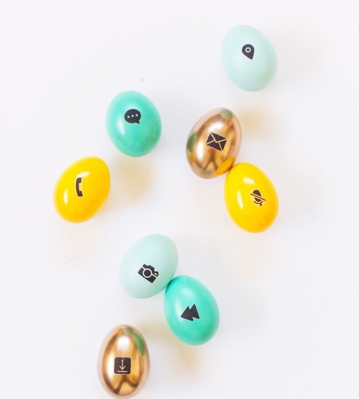 activité créative pour paques, des oeufs colorés en jaune, or et vert et vert clair avec des symboles modernes empreints