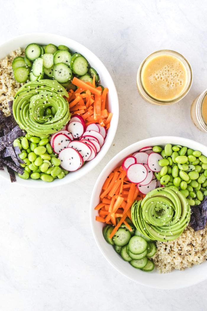 salades dans les couleurs de l'arc-en-ciel, avocat, concombres, carottes, haricots verts, jus d'orange, avoine, dîner salutaire, deux pots blancs avec de la salade hyper coloré avec un mix de légumes