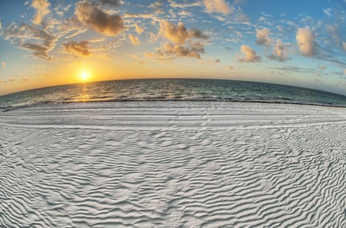 paysage de reve, endroit paradisiaque, dunes grises au lever du soleil, nuages éparpillés comme des bouts de coton dans le ciel bleu