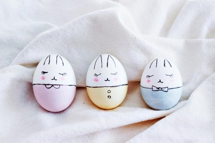 modèles d'oeufs décorés à design lapin de paques, coquilles blanches bicolore avec visages dessinés en marqueur noir