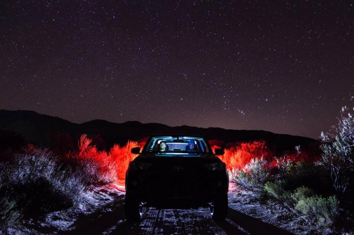 voiture dans le désert d'Arizona en pleine nuit, deux personnes dedans qui contemplent le ciel étoilé, végétation illuminée en rouge par les phares de la voiture