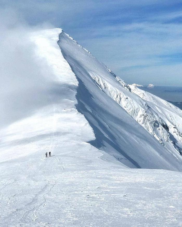 jolie paysage, beau paysage, montagne toute en neige, deux personnes qui marchent vers le sommet blanc et un ciel aux nuages blancs qui ressemblent a un voile, horizon a moitie visible a coté de la montagne