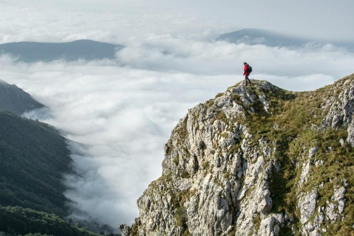 homme en veste rouge au sommet d'une roche montagneuse, nuages blancs, décor impressionnant, silhouettes montagneuses en pénombre