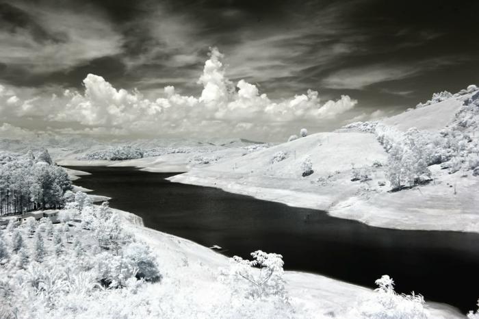 fond ecran paysage, beau paysage, un fleuve en hiver, des nuages blancs sur le fond d'un ciel en gris foncé, photo en noir et blanc