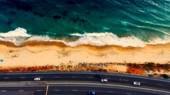 plus belle plage du monde, mer en vert émeraude avec des ondes blanches, beau paysage, sable jaune, route qui passe tout au long de la plage