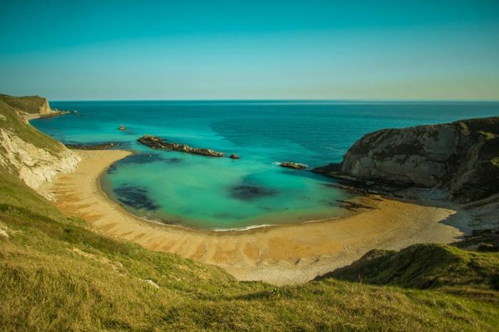 fond ecran paysage, océan en vert et bleu, lagon entouré de roches argileuses, ciel bleu sans nuages, herbe verte ici et la sur les roches