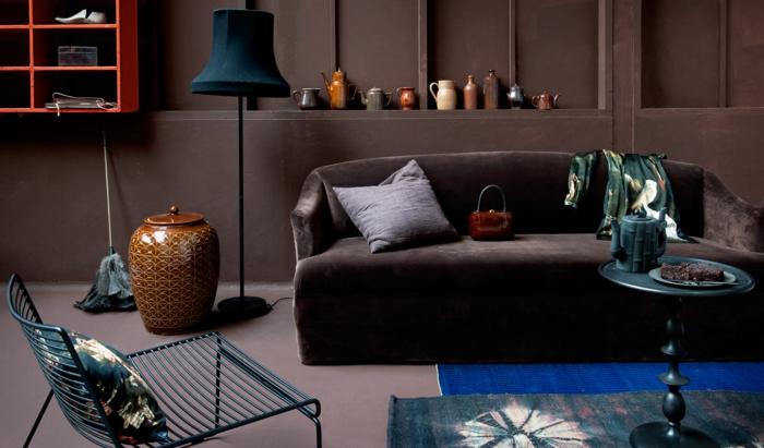 sofa et mur couleur lie de vin, tapis bleu, table bleue, étagère rouge, grande lampe de sol bleue