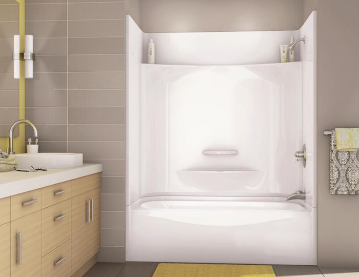 salle de bain avec baignoire encastrée dans mur beige taupe clair et carrelage mural gris clair