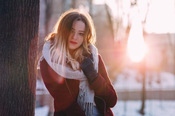 modèle de manteau rouge avec fermeture éclaire combiné avec gants de cuir noir et écharpe longue grise avec franges, cheveux longs avec ombré en blond blanc