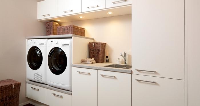 meuble buanderie à design simple de couleur blanc avec poignées métalliques et comptoir gris clair, modèle d'éclairage led sous meubles