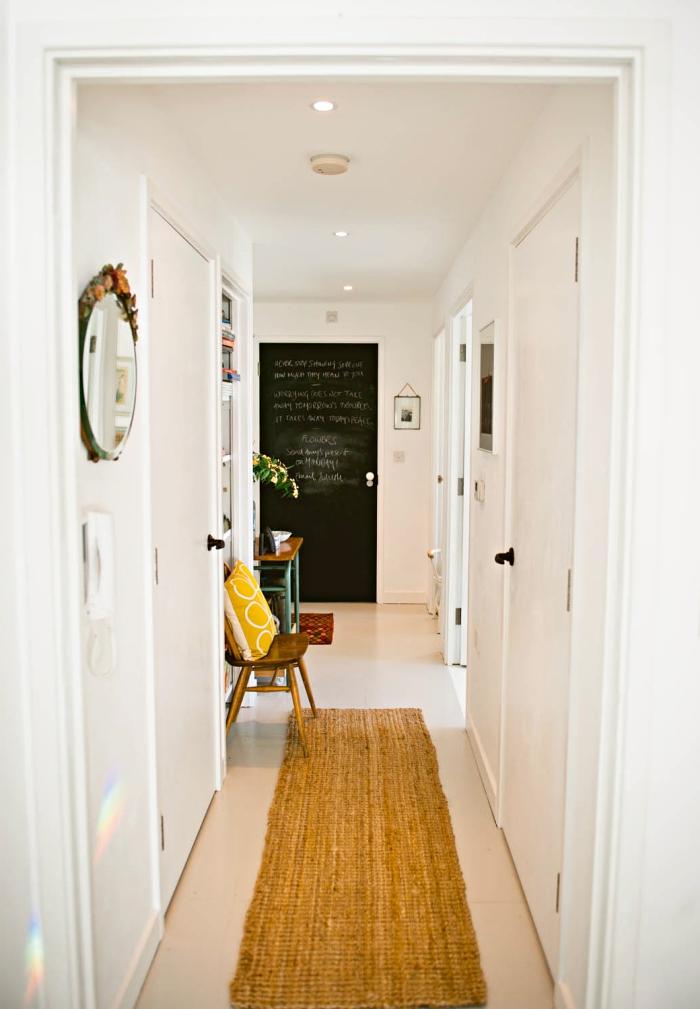 aménagement couloir en blanc avec tapis beige et porte en peinture ardoise, décoration avec coussin jaune et miroir rond