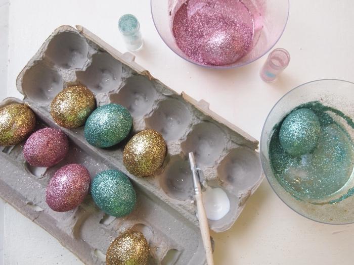 comment décorer les oeufs avec peinture glitter de nuance or rose et vert, récipient à l'eau et peinture glitter