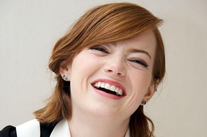 emma stone avec une frange sur le coté, coupe carré court cheveux roux courts, femme qui sourit