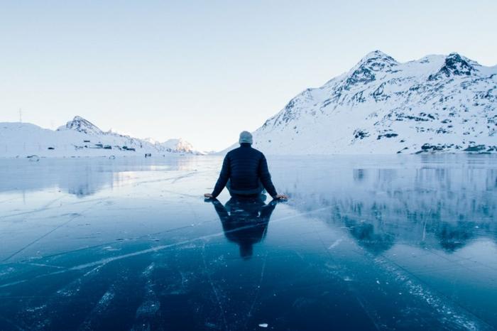 paysage nordique, Alaska, homme assis sur la glace, contemplant les montagnes en neige devant soi, grand bleu