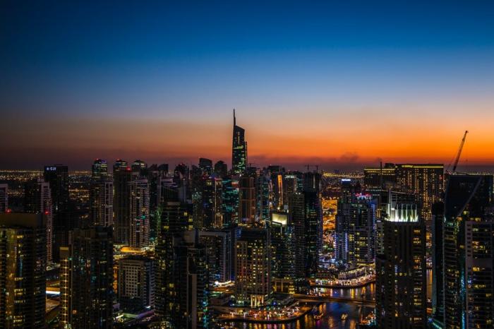 paysage urbain, high tech, ville aux mille lumières, ciel en bleu et orange, des gratte-ciels, sur le fond d'un horizon en orange, soleil couchant