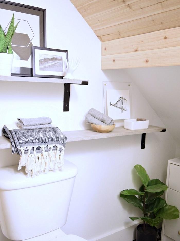 salle de bain avec des rangements au dessus du wc, plafond en bois blond, wc blanc, deco de cadres et plantes