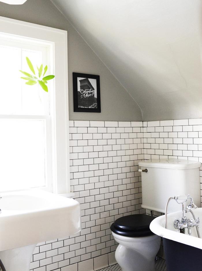 exemple de salle de bain petite surface, carrelage metro blanc, plafond gris en pente, baignoire noir et blanc, lavabo blanc