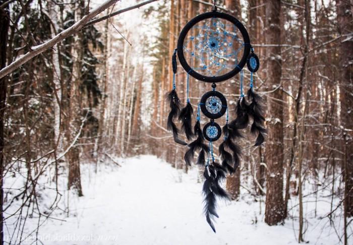 attrape reve indien original cerceaux tailles diverses couleur noire, filet bleu, petites plumes décoratives, fond enneigé