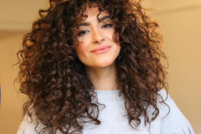 coupe cheveux bouclés longs, une coiffure volumineuse avec des boucles serrés envahissant le visage