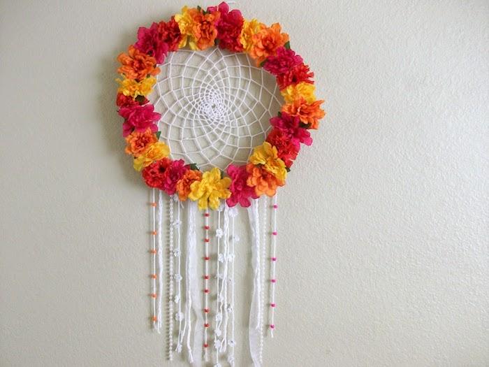 décoration murale fleurie, fabriquer un attrape reve en couronne de fleurs colorées avec filet blanc et des chutes de laine et perles colorées