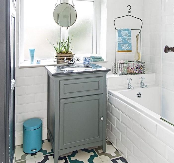exemple de petite salle de bain avec baignoire à encastrer, meuble gris, carrelage mur blanc et carrelage sol à motifs retro, petit miroir rond