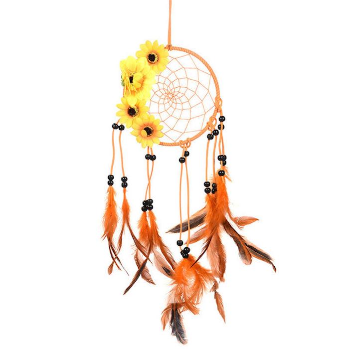 petit capteur de rêve orange avec décoration de perles noires, plumes marron et orange et des fleurs jaunes tourne sol