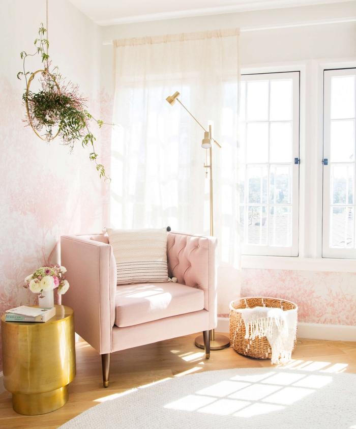 coin de lecture dans une chambre rose avec grande fenêtre, aménagement pièce avec fauteuil rose et table dorée