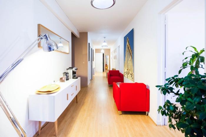 exemple de meuble entrée couloir en couleur vibrante avec fauteuils rouges et plantes vertes, peinture murale en blanc et taupe