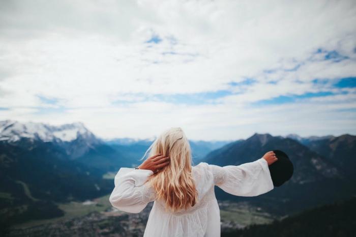 paysage mer, paysage paradisiaque, femme aux cheveux longs blonds en tunique blanche avec chapeau noir a la main, qui regarde l'horizon, grande plaine qui se dévoile en bas