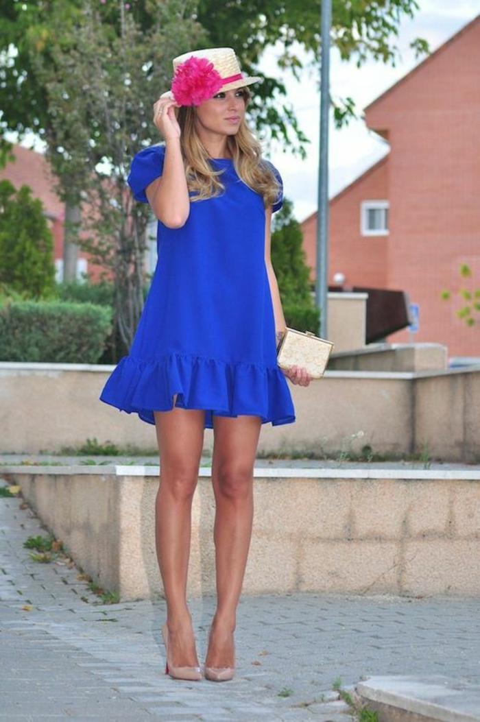 robe en bleu roi avec volants sur les ourlets, robe habillée, chaussures pointues beiges, chapeau de paille enroulé de tissu fuchsia avec une grande fleur fuchsia, petite pochette couleur or