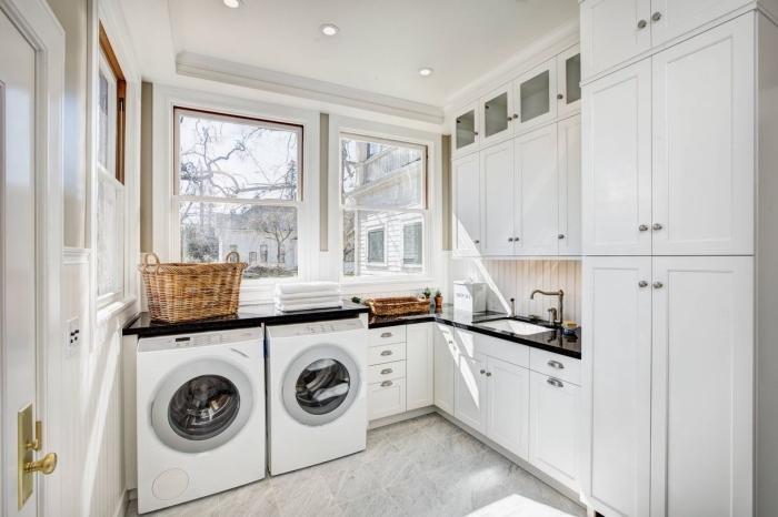 amenagement cellier avec meubles de bois et de verre en blanc avec poignées métalliques, pièce claire avec grandes fenêtres