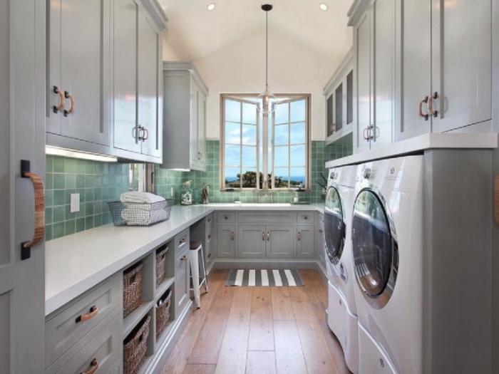 pièce pour rangement balai et lavage avec plan de travaux en blanc et meubles de bois peints en gris aux poignées de bois clair