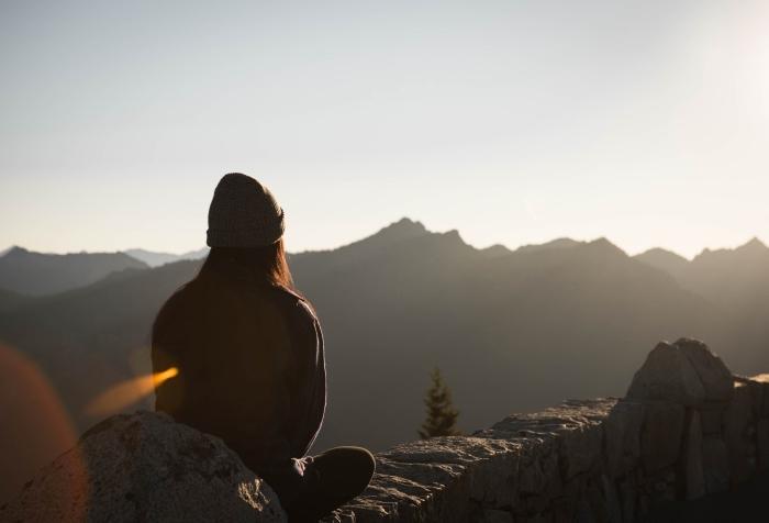 beau fond d écran avec fille habillée en pull et bonnet, comment méditer en plein air au lever du soleil, vue vers les montagnes