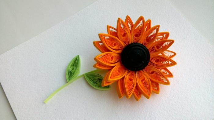quilling fleur, un tournesol orange avec feuilles vertes et tige verte