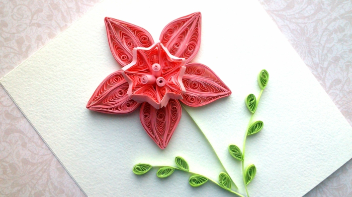 pliage de papier original, jonquille rose avec des pétales originales sur une carte de voeux