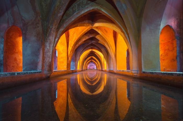 les souterrains d'une église gothique, arches grises illuminées par une lumière jaune, espace mystique, canal d'eau qui reflète les arches