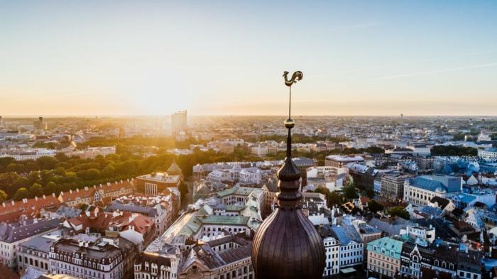 le sommet d'une église avec un coq en bronze, ville européenne, ciel bleu clair sans nuages, ambiance d'été, soleil qui se lève