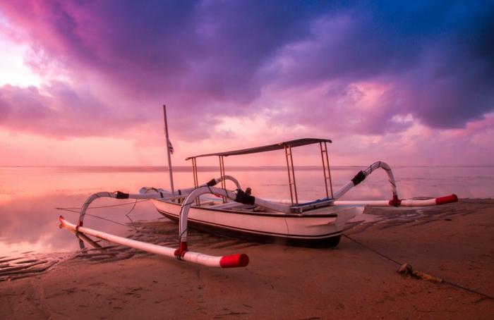 une barque modernisée au bord de la mer. ciel en rose et pourpre, eaux tranquilles, sable marron clair, lumière magique