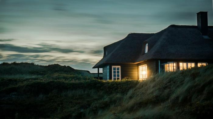 une maison a l'américaine dans la prairie, ciel au nuances vertes, herbe très haute, fenêtres illuminées de manière mystérieuse, paysage paradisiaque