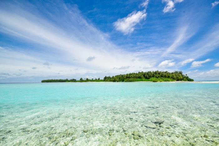 une île dans l'Océan Indien, paysage paradisiaque en vert et en couleur turquoise, ciel rayonnant de soleil avec des nuages qui ressemblent a des voilages délicats