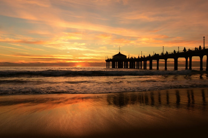 une baie au coucher du soleil, plage déserte en fin de journée, au soir, nuages en orange, pont en bois qui entre dans la mer