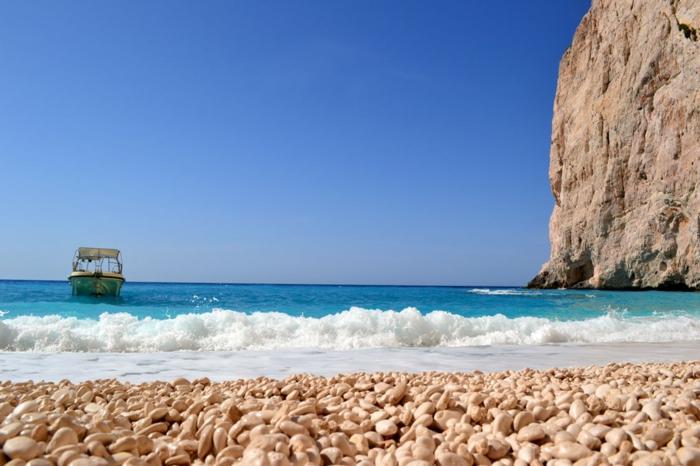 barque qui approche la plage, des eaux en bleu, paysage paradisiaque, roche en argile qui s'élève sur la plage, des petits cailloux blancs ovales sur la plage
