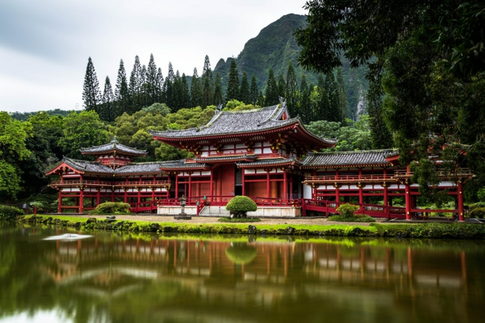 Chine, pagodes rouges parmi une foret, réflexions dans l'eau, vert clair, arbres en été, ciel bleu pastel avec des nuages délicats