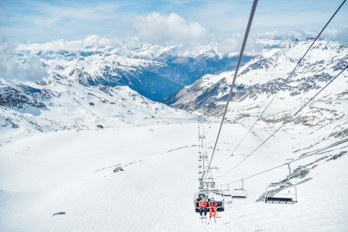 des skieurs en montagne qui montent vers le sommet pour faire une descente en ski, ciel bleu avec des nuages
