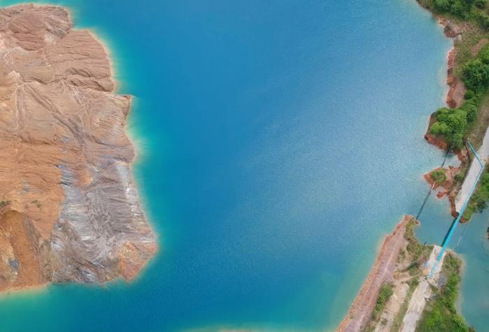 eaux bleues, roches en marron clair, pont bleu, vue d'une baie du ciel, ambiance de vacances, arbres verts, paysage paradisiaque
