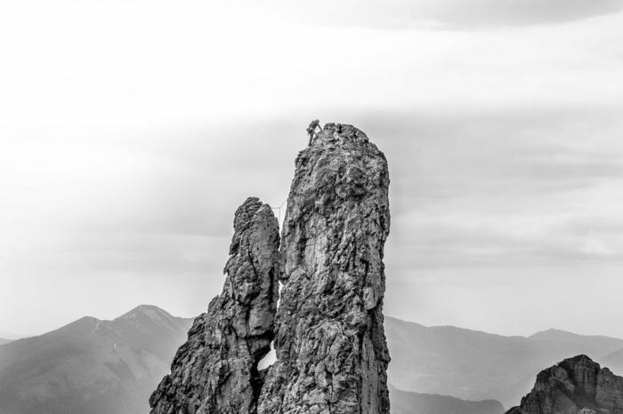 paysage paradisiaque, paysage de reve, roches en gris, alpiniste qui grimpe sur le rocher le plus haut de l'image, photo en noir et blanc, silhouettes de montagnes grises a l'horizon