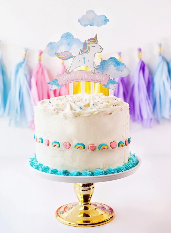 jolie décoration de gateau licorne 1 an avec un cake-topper personnalisé et des bonbons arc-en-ciel sur les côtés