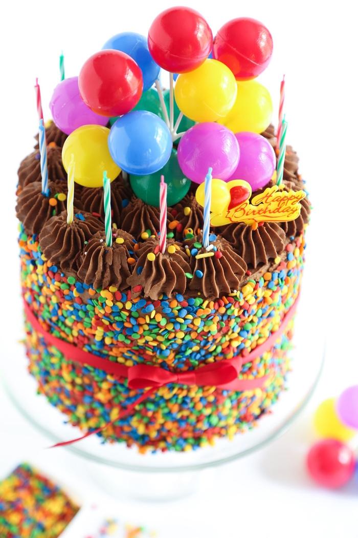 recette de gateau d'anniversaire facile au chocolat avec bougies multicolores et confettis décoré de mini-ballons et d'un joli ruban rouge