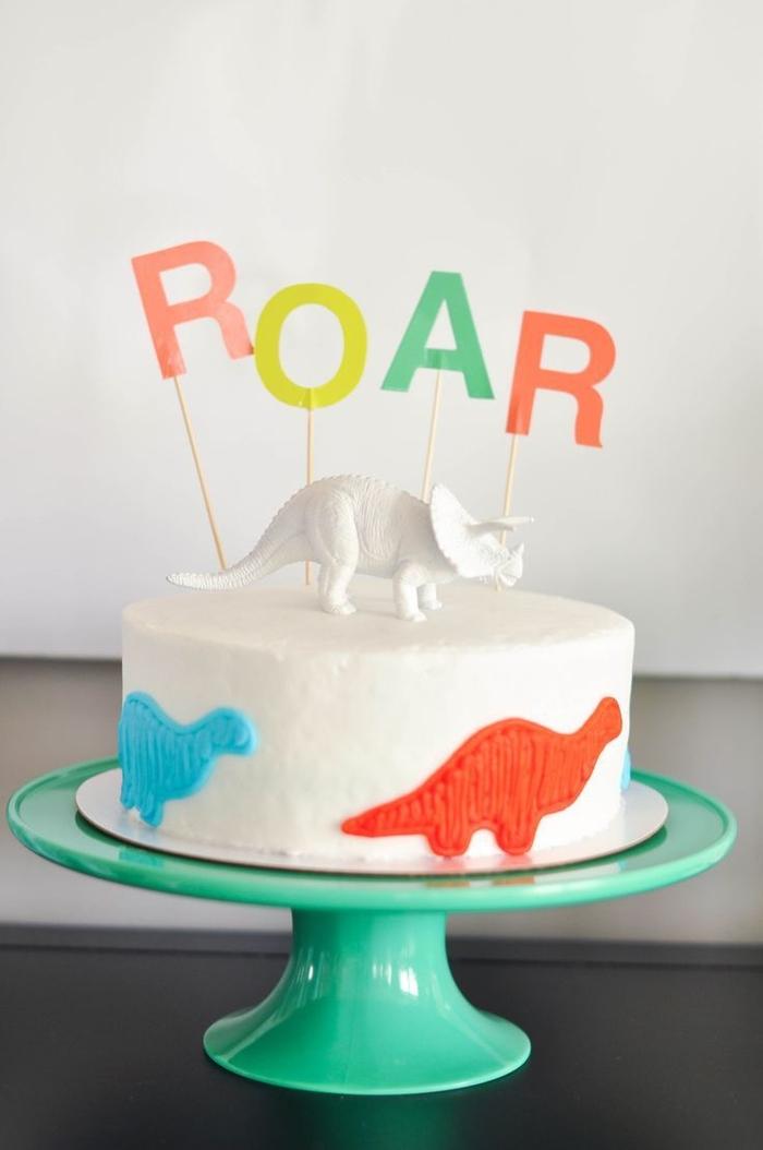 joli design de gâteau d anniversaire garçon au glaçage blanc décoré sur les côtés de petits dinosaures
