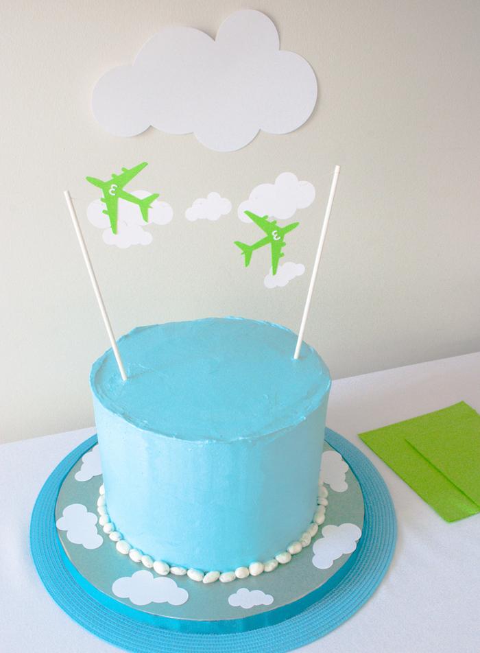 anniversaire sur thème avions avec un gateau d'anniversaire garçon au glaçage bleu décoré avec des cake-toppers avions et nuages en papier